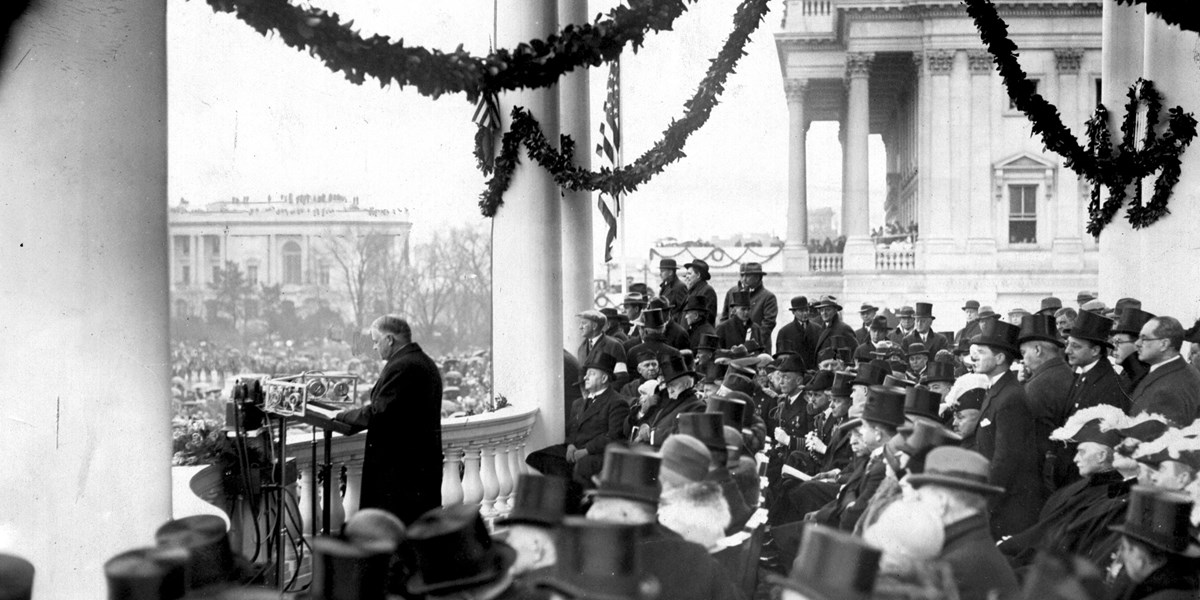 Dignitaries in formal suits and top hats surround Herbert Hoover as he speaks among the pillars of the White House.