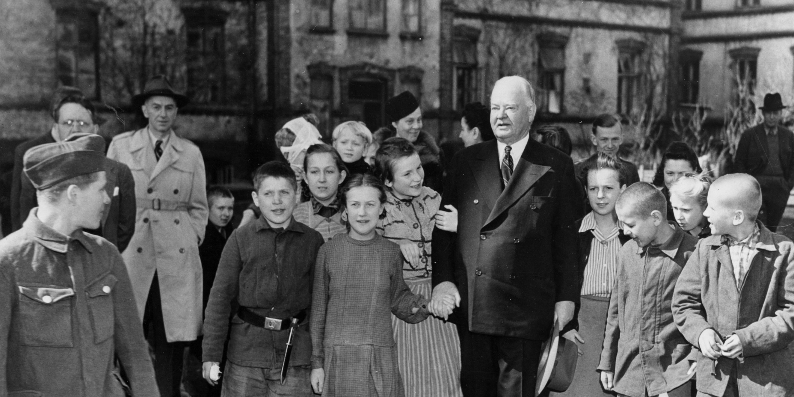 Admiring children surround an elderly Herbert Hoover during a visit to Warsaw.