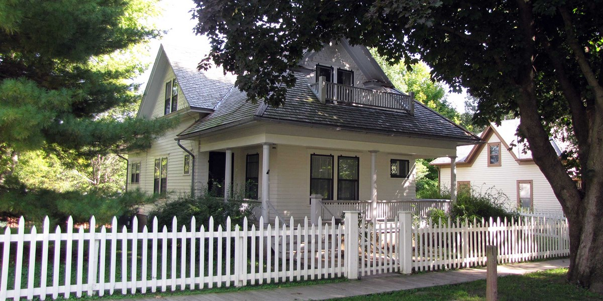 A picket fence encloses a white two-story house with a porch.