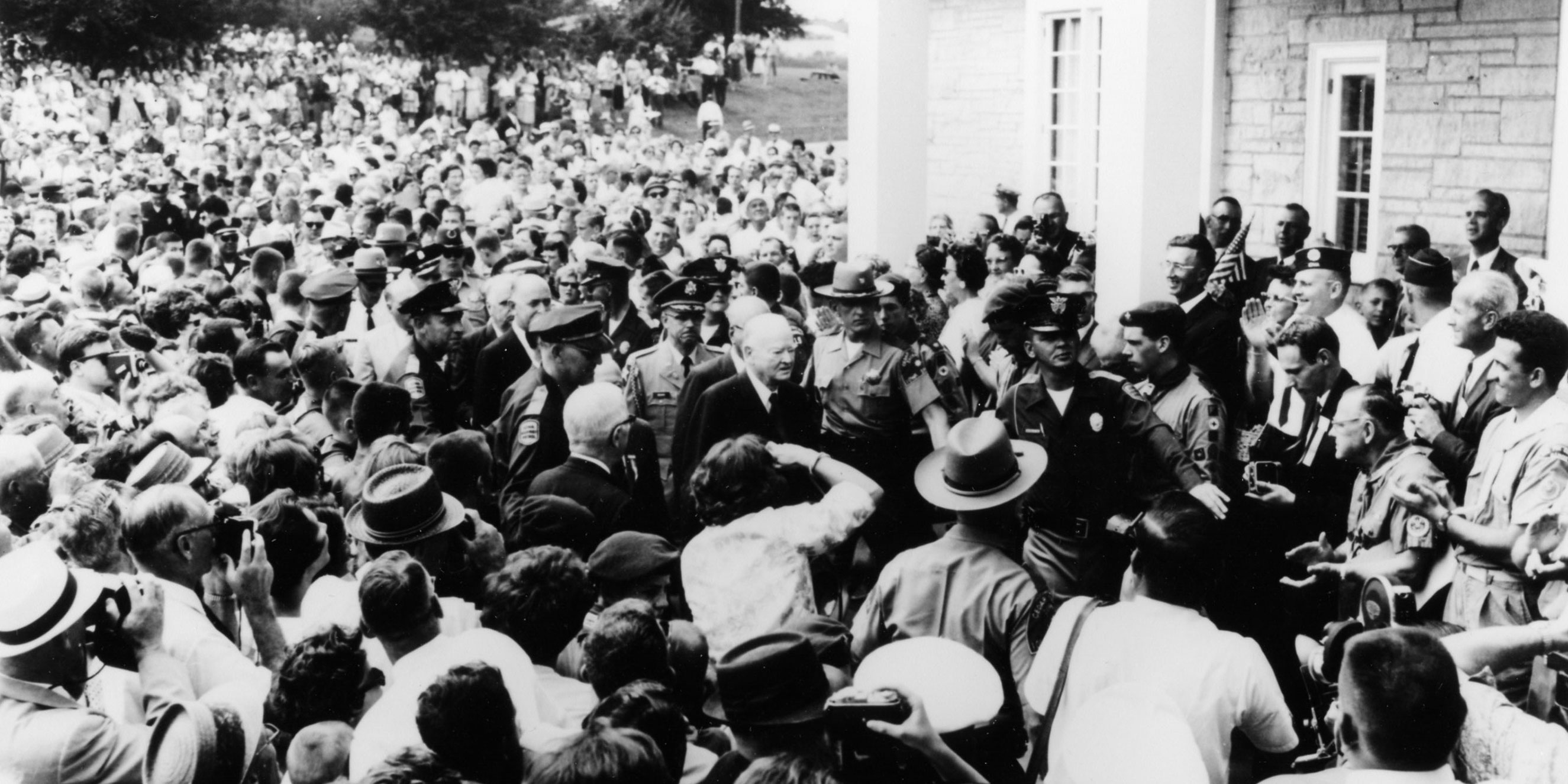 A large crowd surrounds several men in front of a stone museum with white columns. at the Hoover museum dedication, 1962