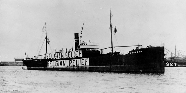 A 1919 photo shows a cargo ship with Belgian Relief printed on huge banners draped on its sides.