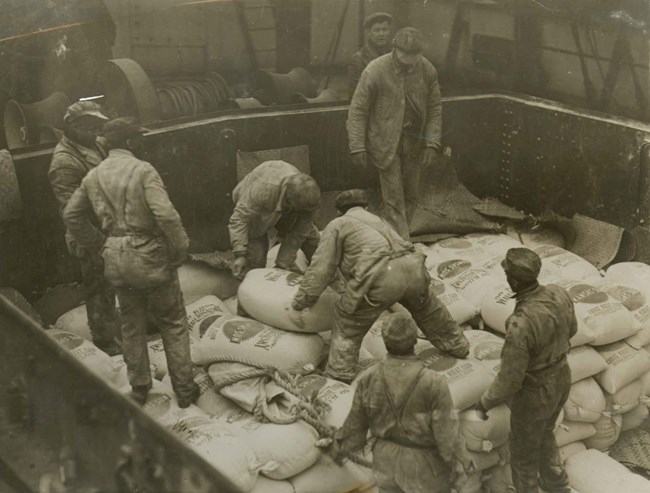 Workmen load a ship with sacks of donated flour.