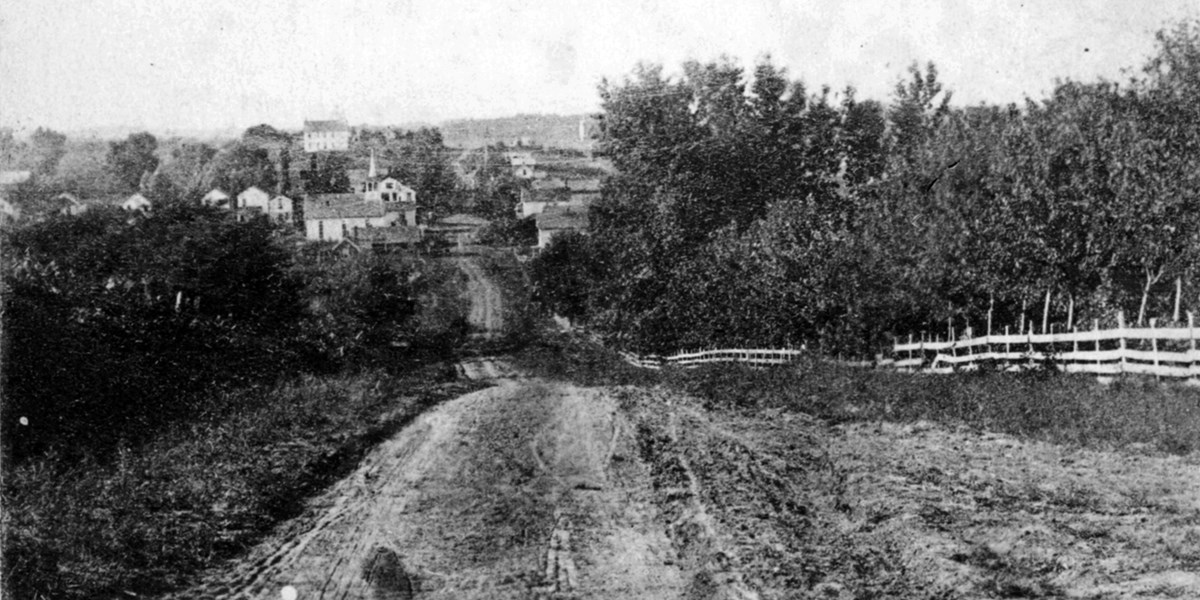 An 1870s photograph of a small town seen from the top of a hill.