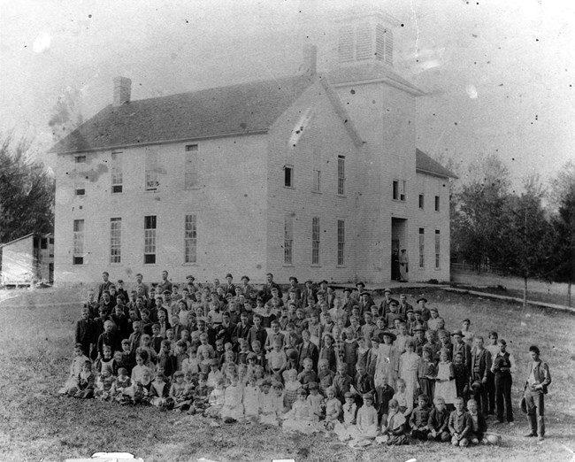 Several dozen schoolchildren of all ages in 1800s clothes pose for a photograph in front of their school building.