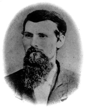 Oval-cropped black-and-white portrait photograph of a young dark-haired man with a long beard.