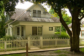 A white two-story house with a porch and picket fence.