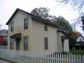 A yellow two story house with a white picket fence.