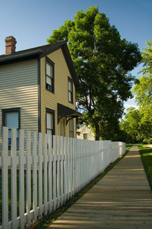 A boardwalk and picket fence near a historic home.
