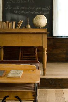 A historic classroom's teacher's desk and blackboard as seen from the pupils' desk.