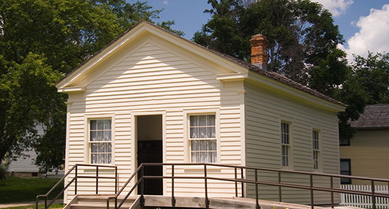 A white one-room schoolhouse in a park setting.