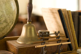A bell, globe, books, and pencils on the teacher's desk of a historic schoolhouse.