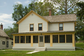 A cream colored two story house with a broad enclosed porch and yellow trim.
