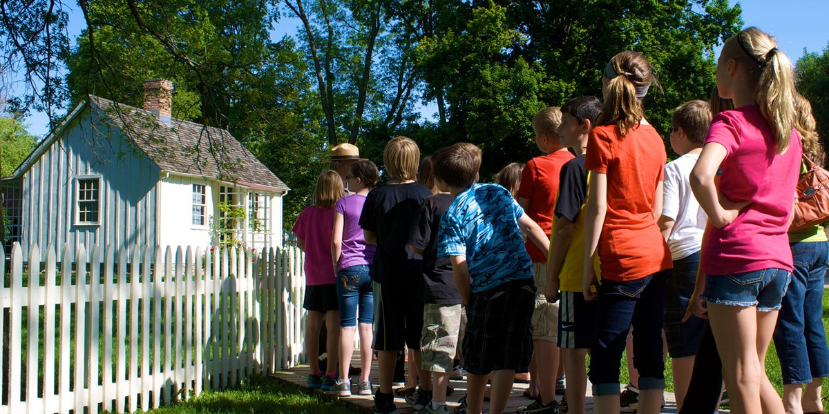 A park ranger talks to school children at a historic cottage.
