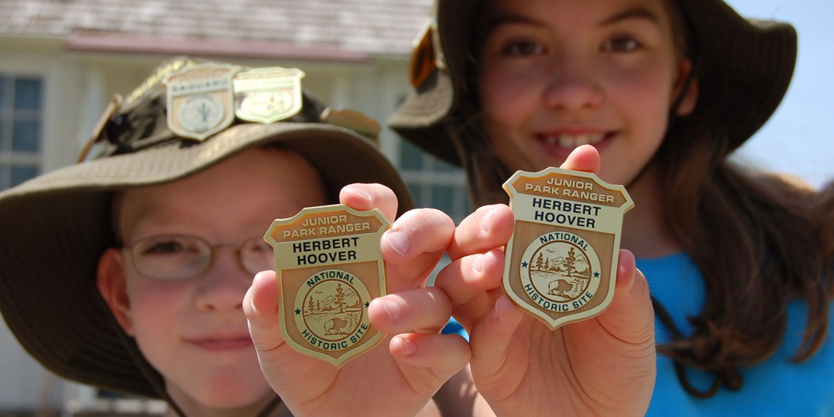 A boy and girl show off their Junior Ranger hats and badges.
