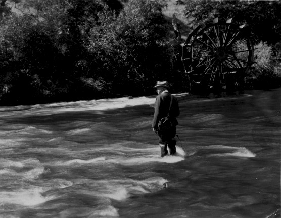 Black and white archive photo of Herbert Hoover fishing in a stream.