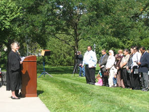 A judge addresses candidates for citizenship on the sunny grass lawn east of the Herbert Hoover Presidential Library and Museum.