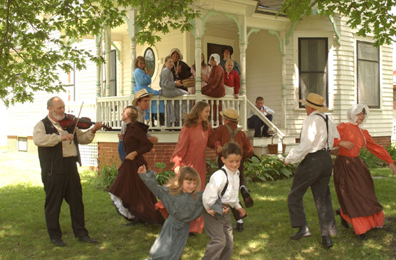 Living history volunteers in 19th century dress dancing to a fiddler.