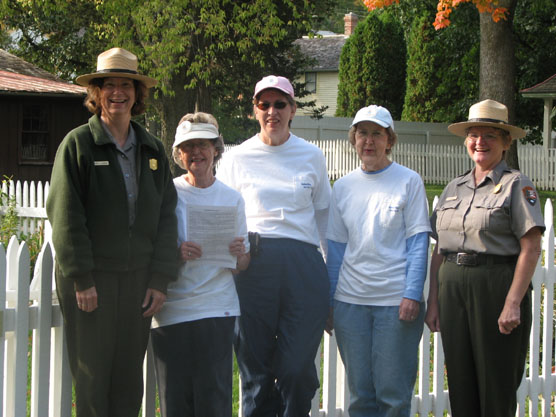 Two women in National Park Ranger uniforms and three women in white Hawkeye Hiker tee-shirts pose by a picket fence.