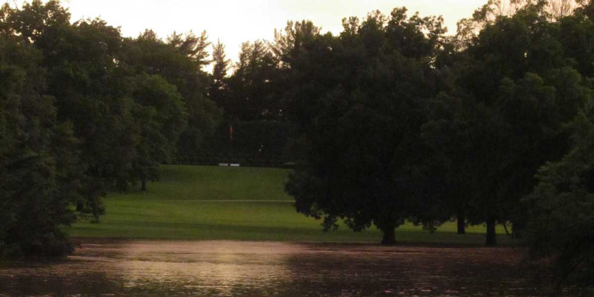 A presidential gravesite overlooks a flooded park at sunset.