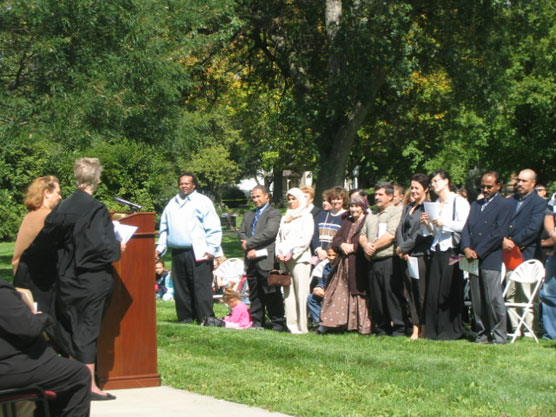 A federal judge and new citizens in an outdoor ceremony.