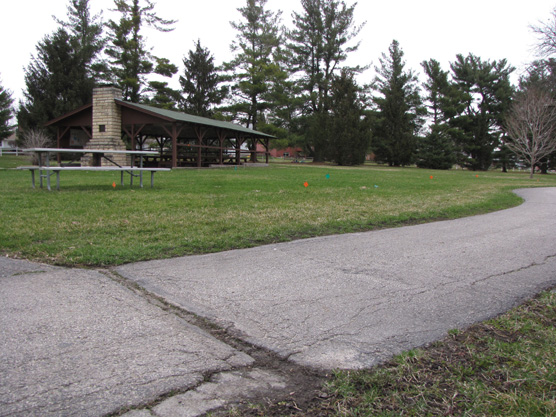 A cracked and buckled asphalt walkway leads past a picnic shelter.