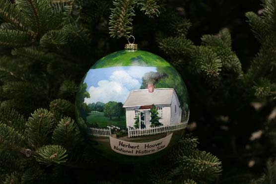 A spherical ornament painted with a scene of a small white cottage hangs from the bough of a spruce tree.