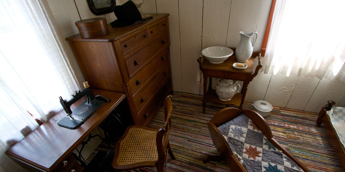 An antique bureau, sewing machine, crib, and nightstand with a pitcher and washbasin furnish a small 1800s bedroom.