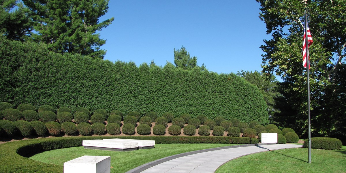 Two plain marble ledgers mark graves in a semicircular planting of landscape shrubs and a United States flag.