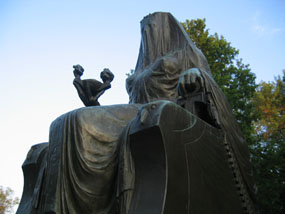 Bronze statue of a seated, veiled Egyptian goddess against the blue sky and trees of fall foliage.