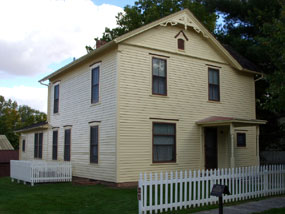 A yellow two story house with brown trim.
