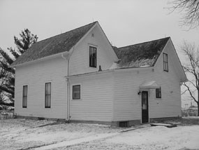 White two-story farmhouse with a double-gabled roof in the snow.