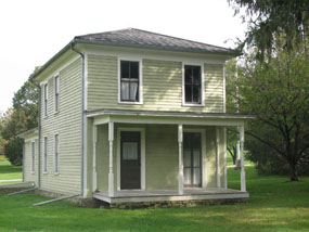 A green two story house with white trim and a porch.