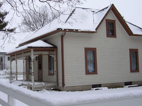 Snow covers the roof and lawn of a two-story cream colored house with brown trim.