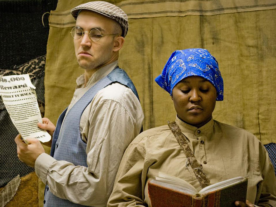 Stage actors in 19th century dress portray a white man and a black woman.