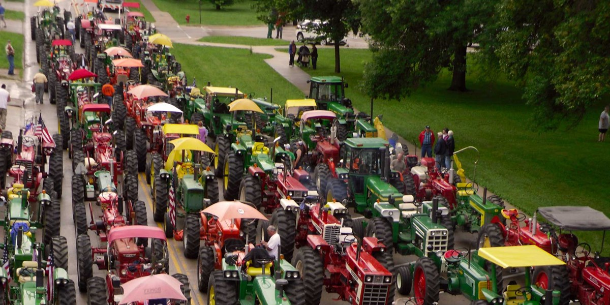 Rows of colorful antique tractors line up for a parade on a street near a park.