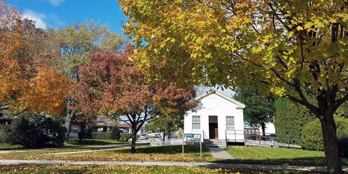 Trees in brilliant autumn foliage frame an old white schoolhouse.