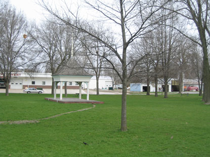 A grassy lawn with a small bandstand and trees.