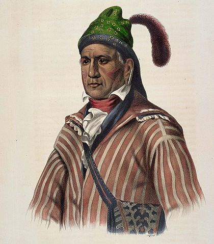 portrait of Native American with red and white striped coat, satchel, green hat with feather, and face markings that appear to be tattoos on cheeks