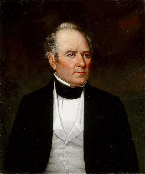 portrait of man from stomach up wearing black jacket, white vest and shirt, partially bald