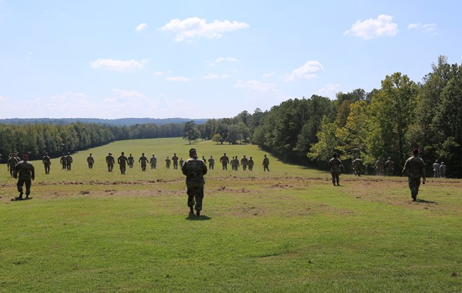 Enlisted military personnel walking away from camera through the battlefield