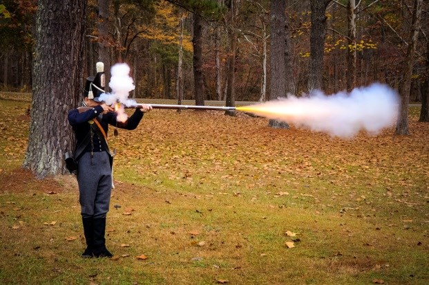a man in period military clothing shooting a musket, smoke and flame coming from pan and barrel