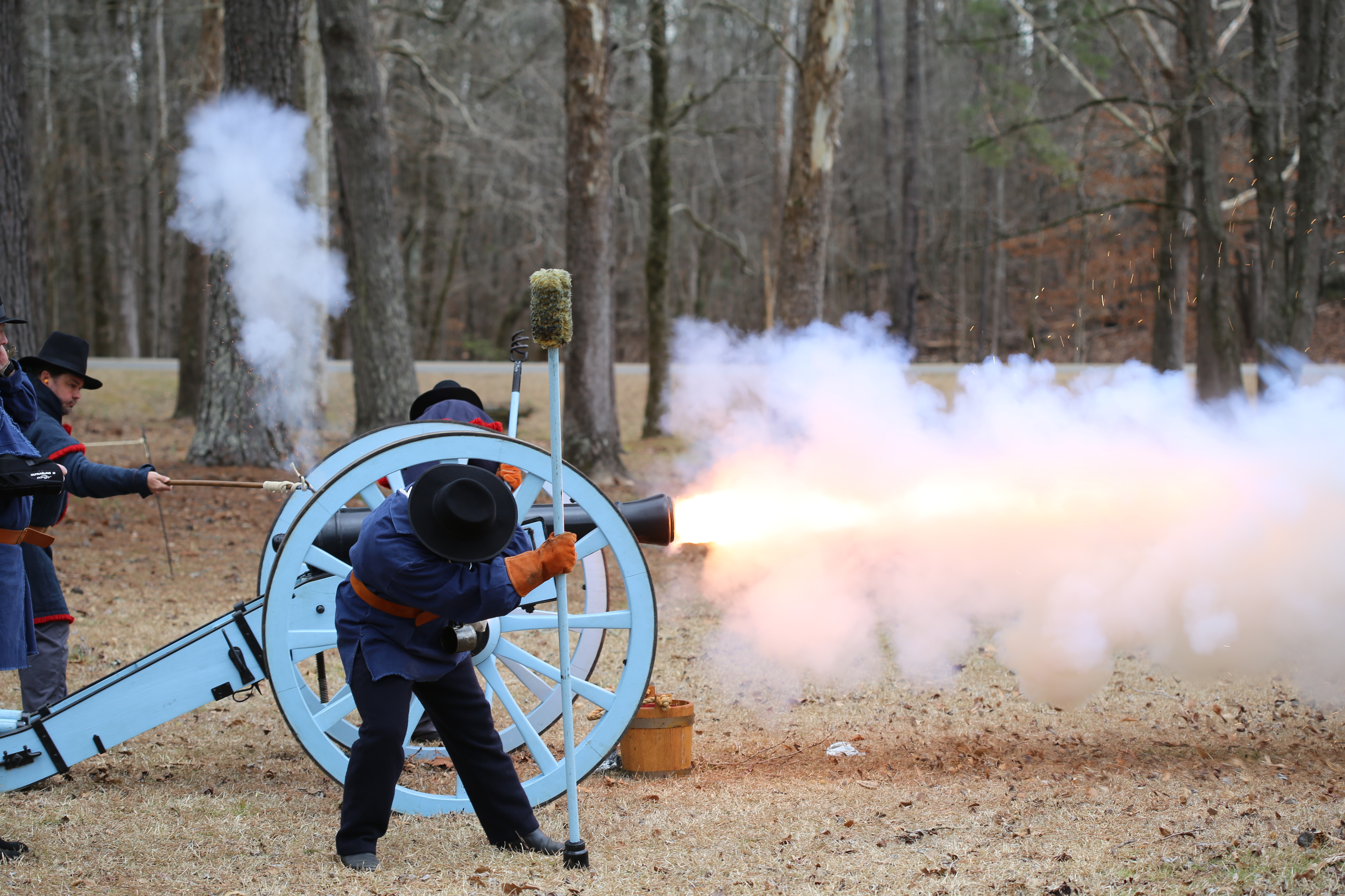 men in period uniforms shooting cannon; smoke and fire coming out of barrel