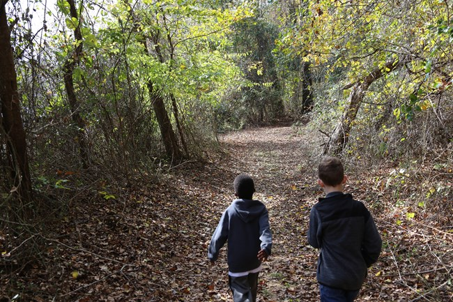 two kids hiking through forest on nature trail