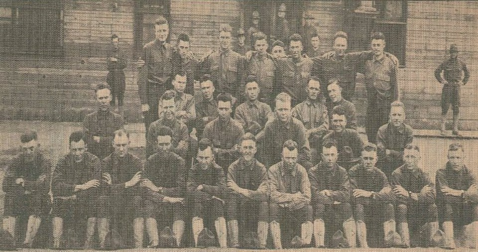Several men standing and sitting for a group portrait in front of a wooden building