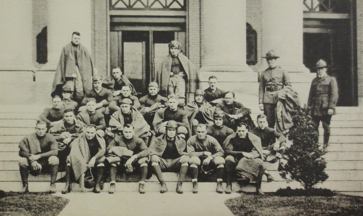 Football players sitting on the steps to a building