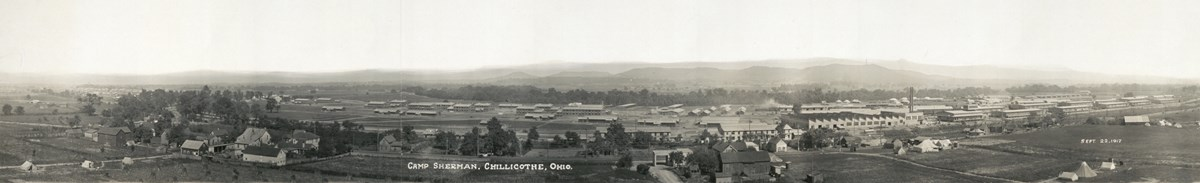 Several large buildings in the foreground with large hills in the background