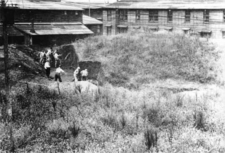 Camp Sherman barracks in background. Mounds being excavated in foreground.