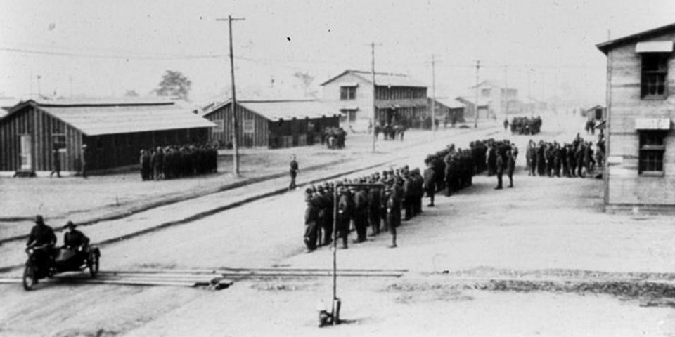Soldiers standing at attention in front of camp buildings