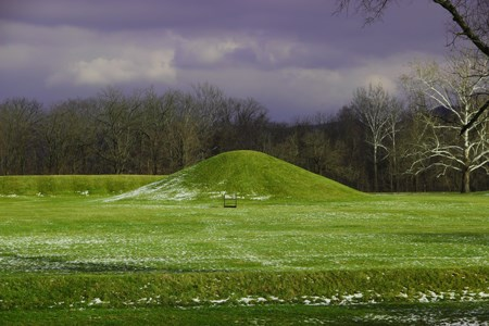 A tall grass-covered mound under a dark grey sky.