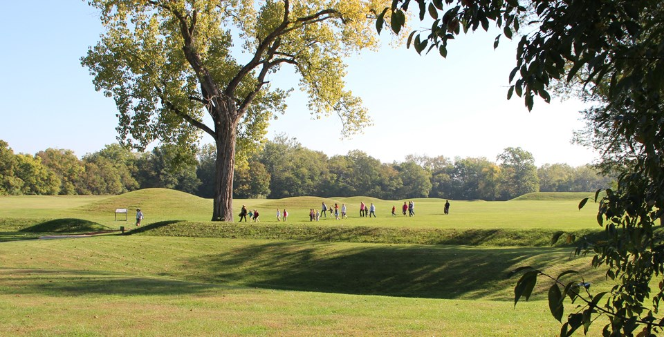 Several people walking around grass-covered mounds
